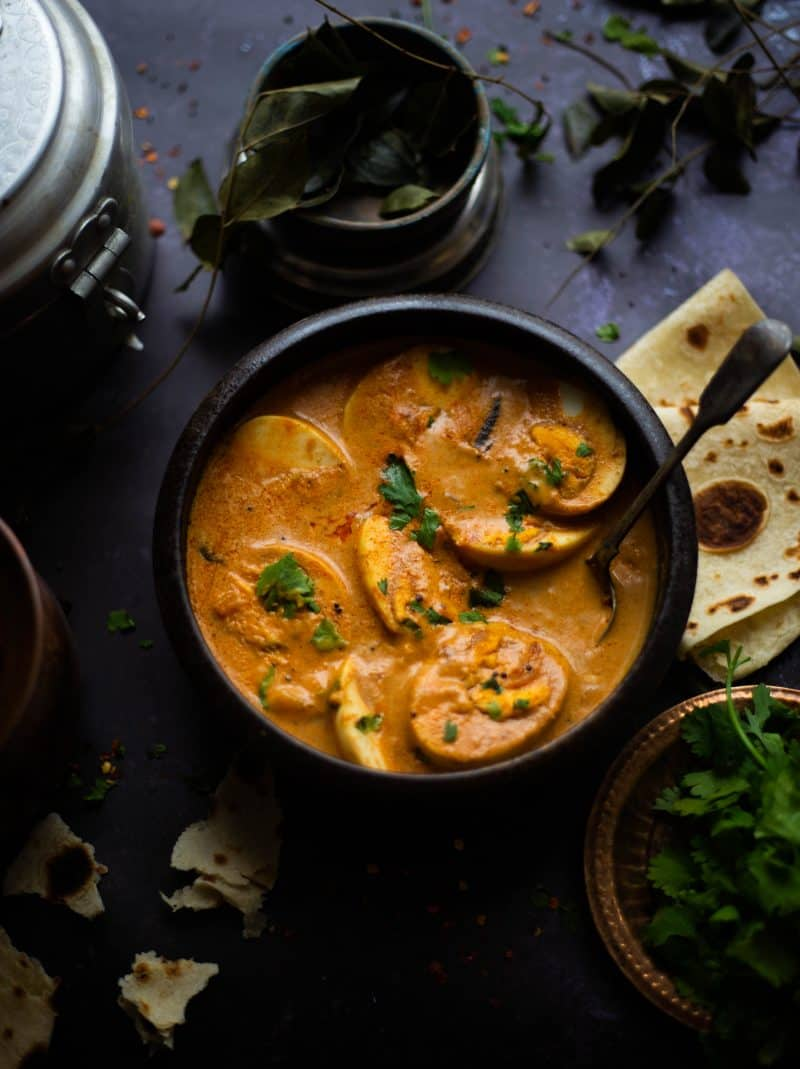 South Indian Style Egg Curry in bowl with spoon and roti to side