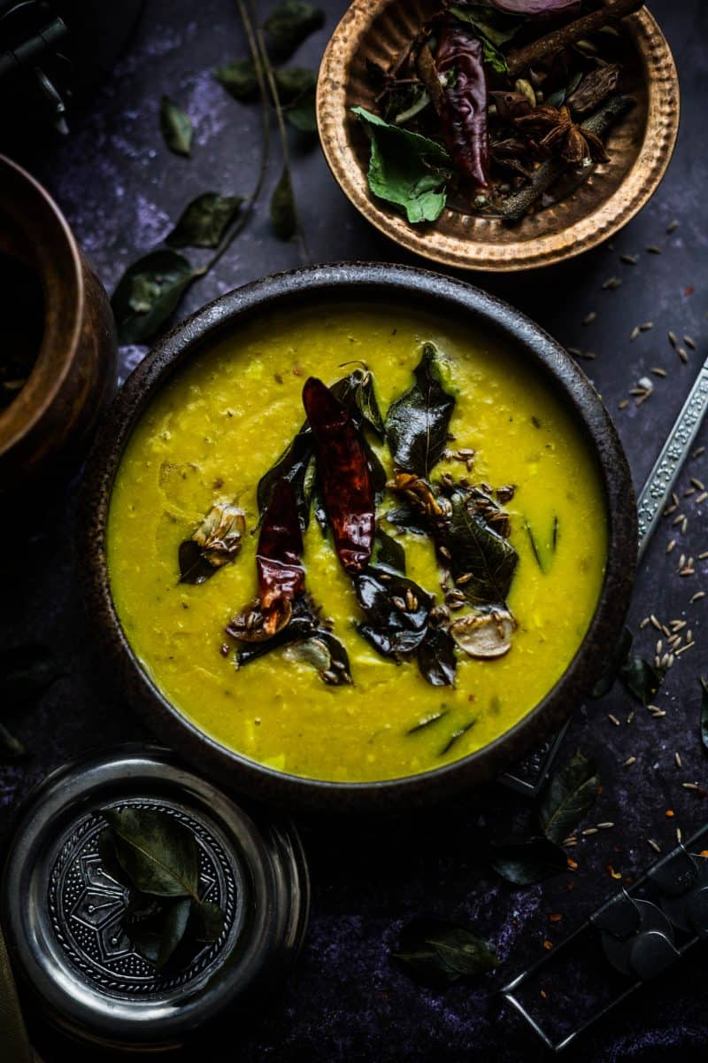 Masoor Dal Tadka in bowl with red chilli, curry leaves, garlic and cumin seeds on top