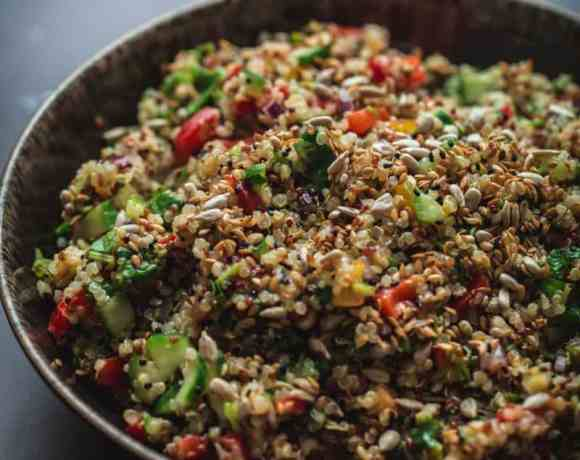 Vegetable and Herby Citrus Quinoa Salad in a bowl on black background
