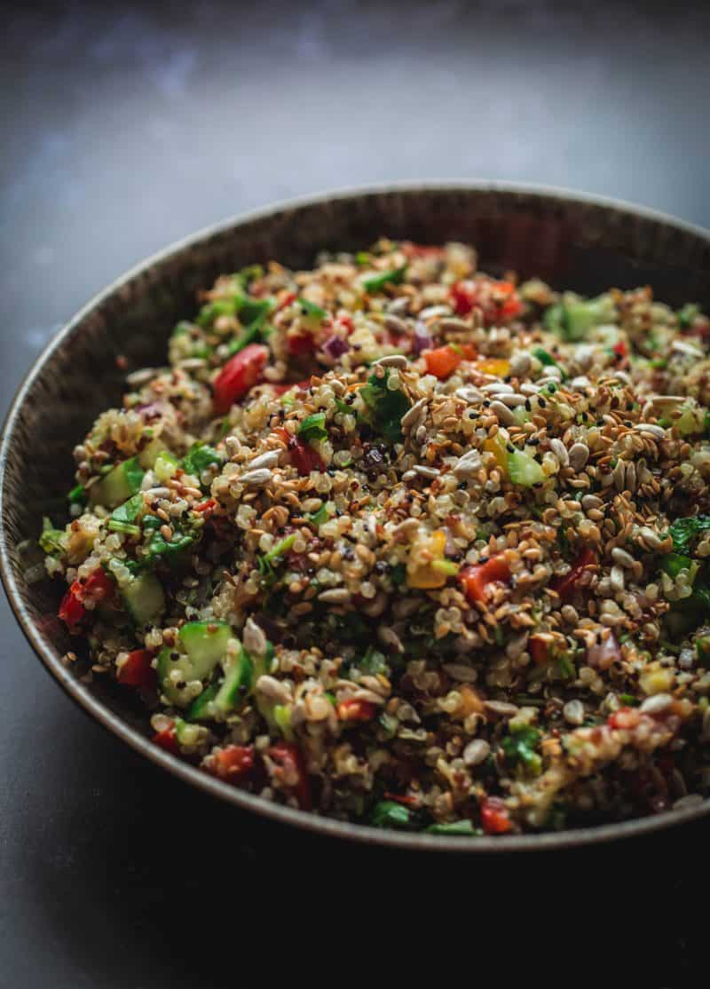 Quinoa with vegetables and salad seed toppings in a bowl on a grey background.