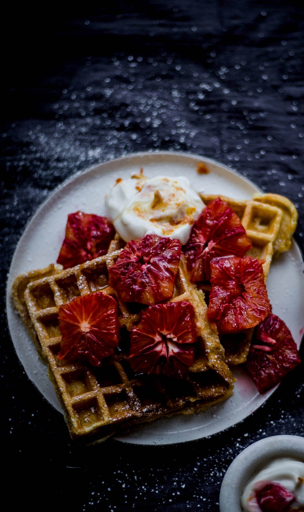 Cardamom and Cinnamon Waffles with Blood Orange Yoghurt and pieces of blood oranges on a plate on a grey background dusted with icing sugar