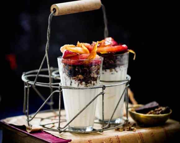Chai Apple and Yoghurt Granola Parfait in two cup in a wire glass carrier on a book with a blue background.