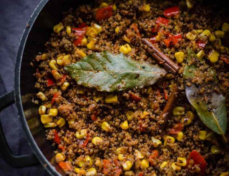 quinoa pilau with indian vegetables in a pot on grey background.