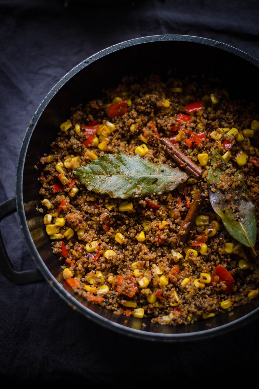 Quinoa with sweetcorn and indian spiced vegetables in a pot on a grey background