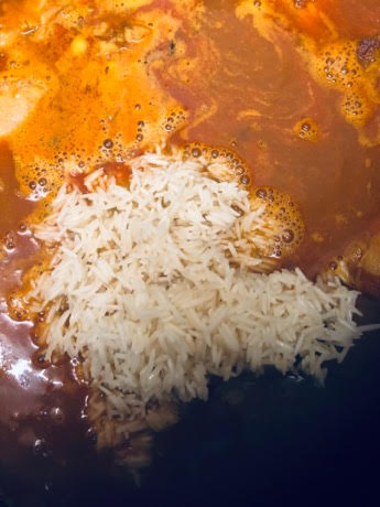 Chicken curry with water and rice on top in large pot