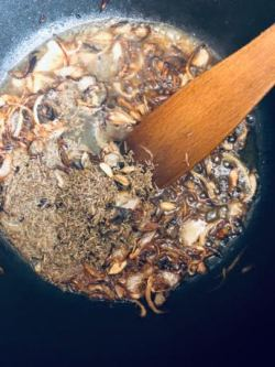 Browned Onions and spices in a pot with wooden spatula