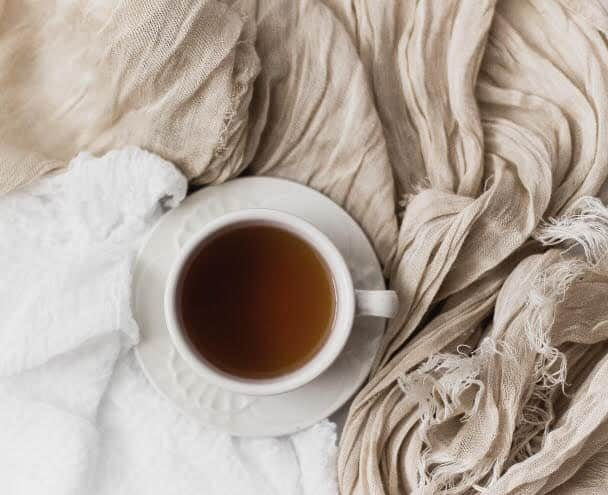 Cup of tea on creased bed sheets