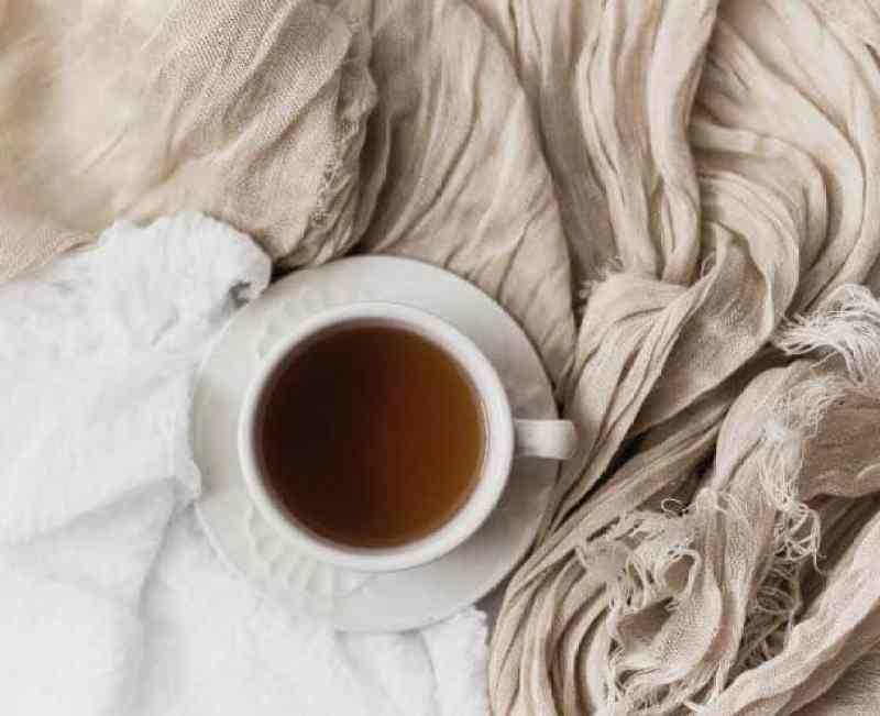 Cup of tea on crumpled bed sheets