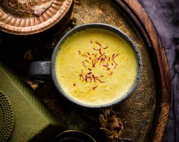 Turmeric and saffron milk in a cup, on gold tray, next to a green cast iron kettle