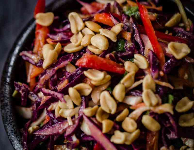 Red Cabbage, Red Pepper, Coriander and Peanuts in a black bowl on a grey towel