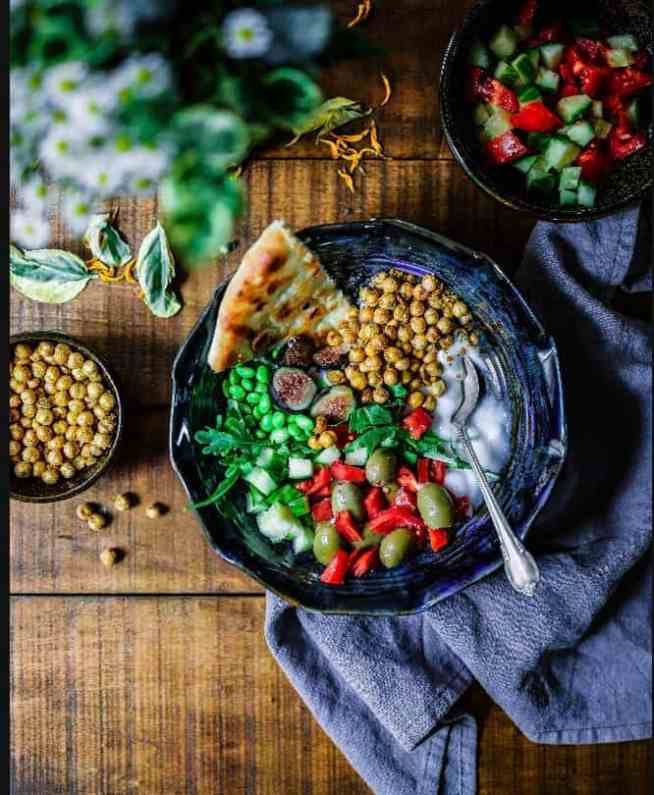 Chickpea and salad bowl with pitta and spoon on towel, chickpeas to side and salad to rear, daisies on table