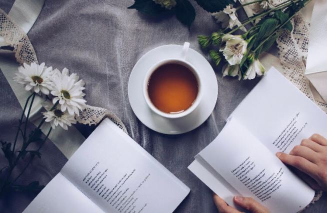 A cup of tea, flowers and hands resting on an open book on a sheer background