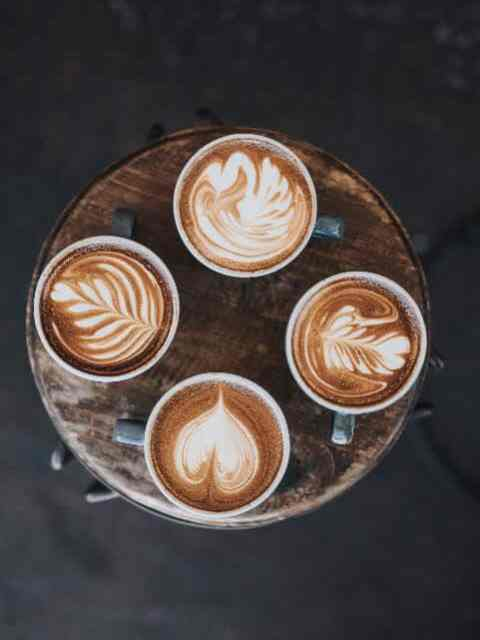 4 cups with latte art on round wood table