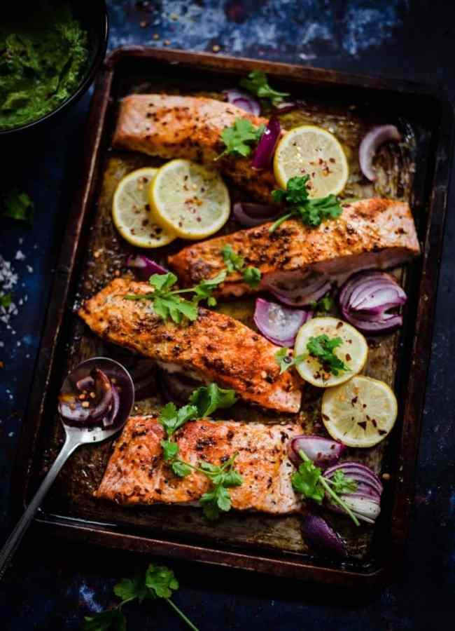 Salmon in a tray with lemons, red onions and coriander