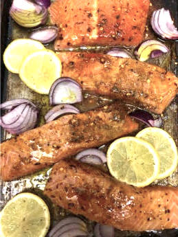 Salmon with marinade with red onions and lemons scattered around