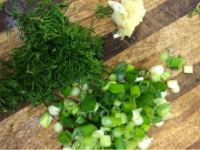 Chopped spring onions, garlic and dill on board