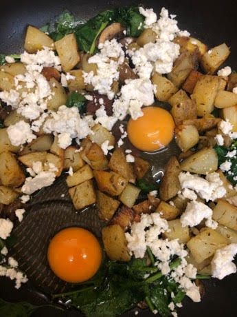 Potatoes, Feta, Spinach, Mushroom in pan and eggs in hollows