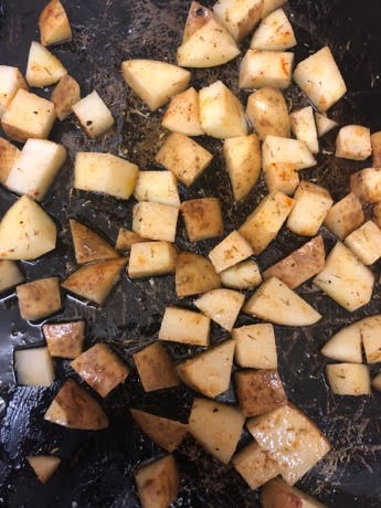 Cubes potatoes with oil on baking tray