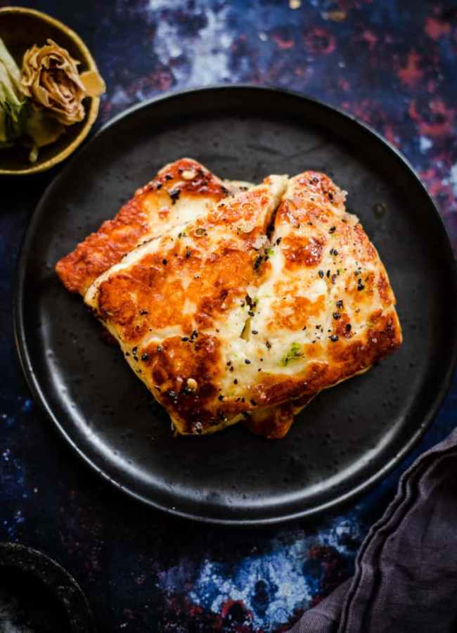 Halloumi slices on black plate with honey and black seed