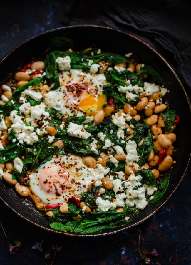 Eggs, Spinach, Butterbeans and Peppers in a dark pan
