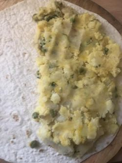 Potato and pea mixture spread on half wrap