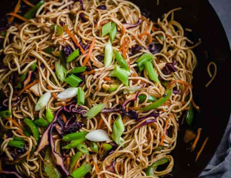 Hakka Noodles in Wok topped with Spring Onions on grey towel