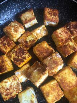 Golden brown Paneer cubes in pan