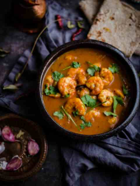 Prawn curry in bowl with roti to side and garlic cloves and curry leaves around