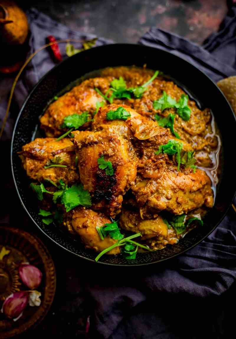 Cooked chicken dish in bowl with coriander on top and spices scattered around the table
