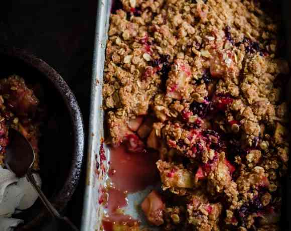 Apple and Blackberry crumble in casserole dish with 1 portion in plate