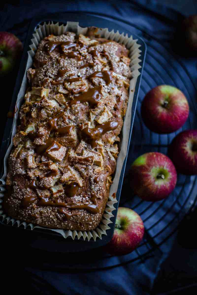 Apple Loaf Cake on wired rack with apples in background