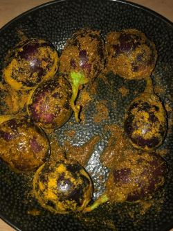 Aubergines marinading in spices in a bowl