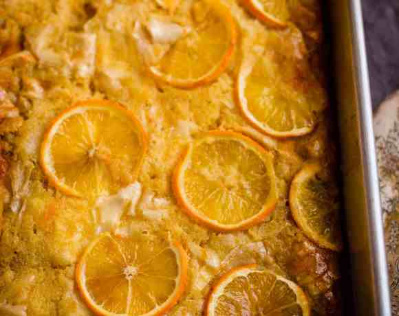 Portokalopita in a tin topped with oranges with a knife to the side