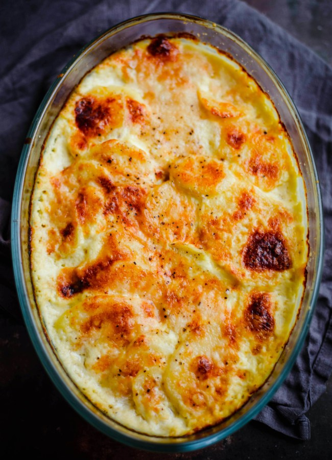 Potato Dauphinoise in oval glass dish on grey towel