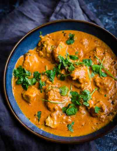 Chicken Makhani in a blue bowl with Coriander garnish