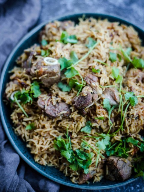 Yakhni Pulao in a dish topped with coriander