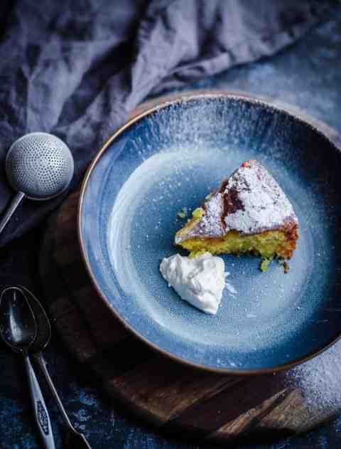Slice of Orange Cake in blue bowl with a dollop of creme fraiche