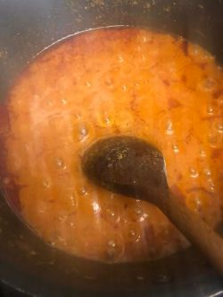 Tomatoes being stirred in pot