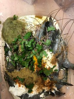 Prawns in a dish with all marinade ingredients on top