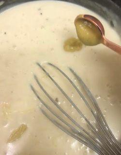 Mustard being added to cheese sauce