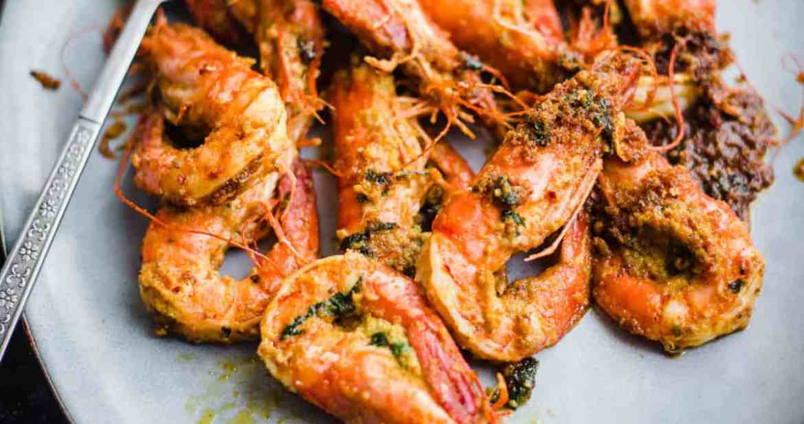 Tandoori prawns in a blue platter with large spoon to side