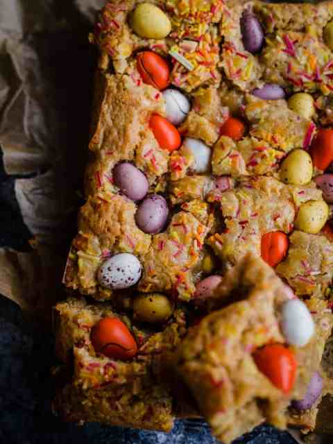 Mini Egg Blondies on baking paper with one piece cut out