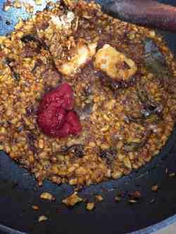 Tomato puree added to wok