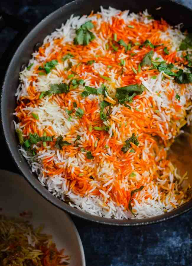 Prawn Biryani in a pot with coriander and coloured rice on top