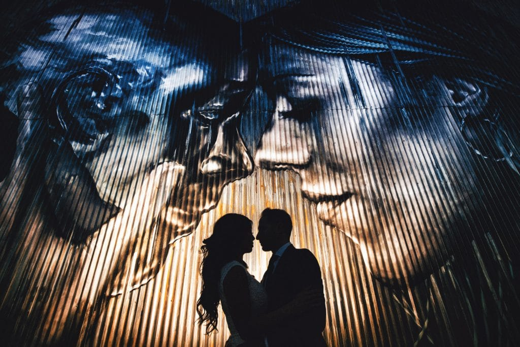 Create Client Experiences:Silhouetted Couple Posed In Front Of Massive Backdrop