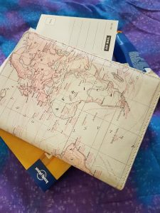 digital detox traditional handwritten travel journal with postcard and lonely planet