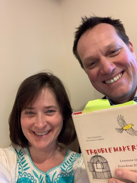 Host Jeanie Phillips (left) and Mike Martin (right) with a copy of Carla Shalaby's book Troublemakers.