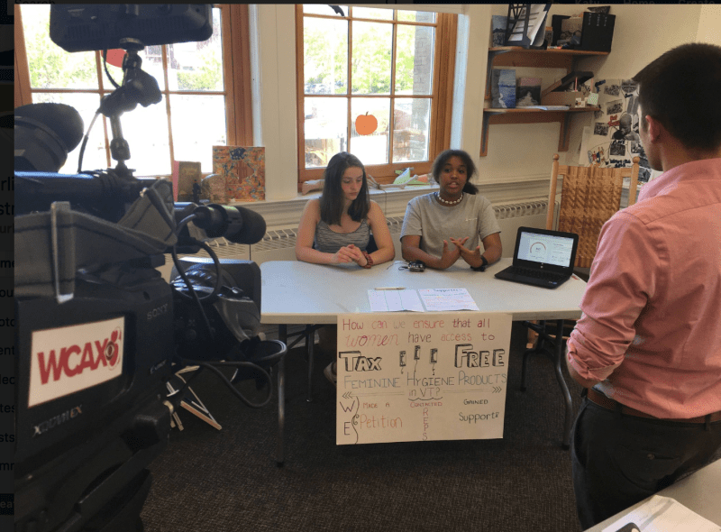 Two students sit behind a desk in a well-lit classroom, speaking to an adult in front of them. A WCAX news camera is also trained on them. From a critical lens on project-based learning.