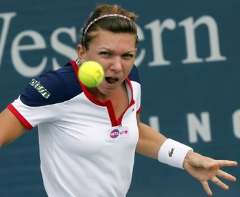 Simona Halep hits a return to Su-Wei Hsieh during their first round match at the women's Cincinnati Open tennis tournament