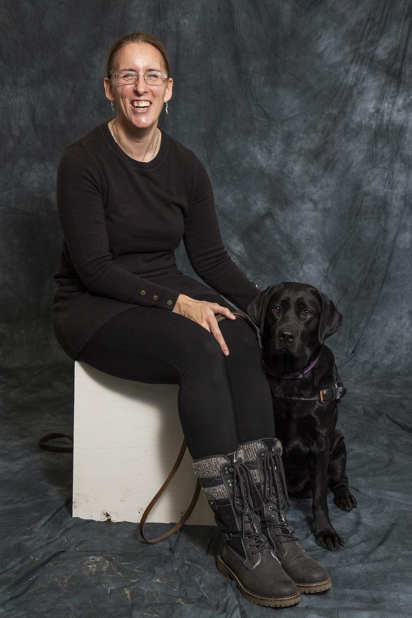 Foto van zwarte Labrador Tarka, die naast Debby op een verhoging zit.